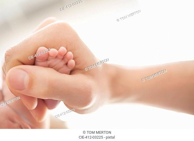 Mother cradling newborn baby's foot