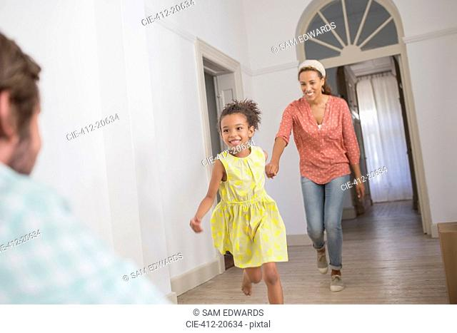 Mother and daughter running towards father