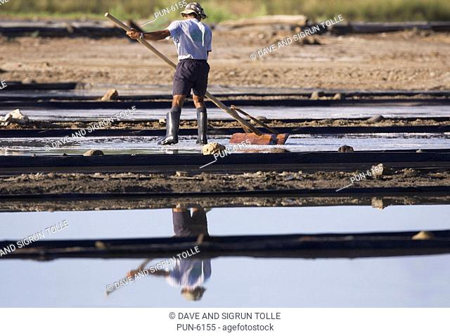 Man working a salt pan or salina
