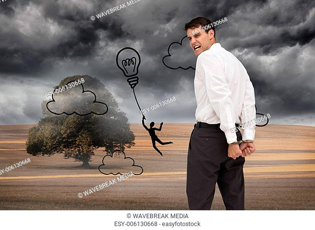Composite image of rear view of young businessman wearing handcuffs