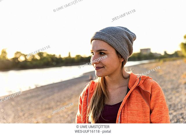 Portrait of a sportive young woman at the river, weraing a beanie hat