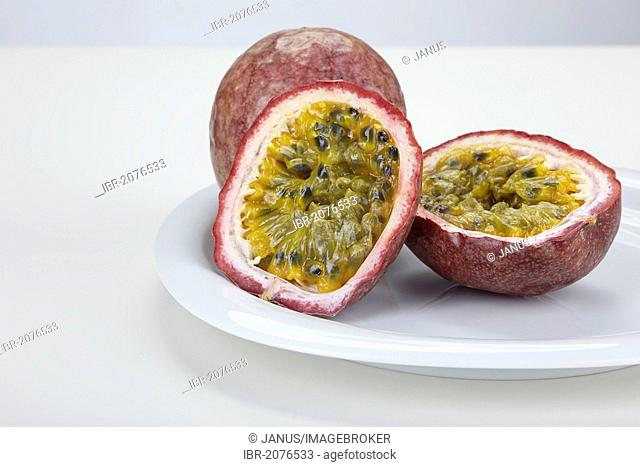 Two passion fruits (Passiflora edulis), one whole fruit and one fruit cut in half, on a white plate
