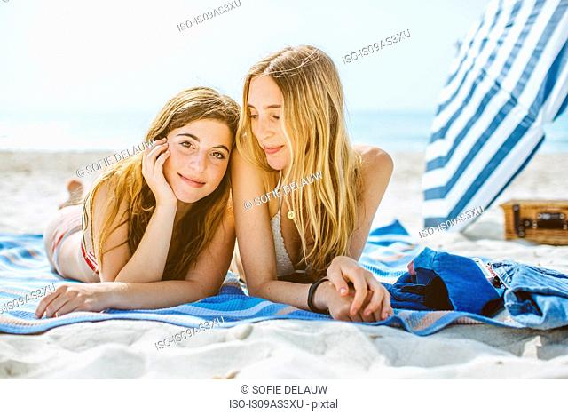 Portrait of two young female friends taking sunbathing on beach