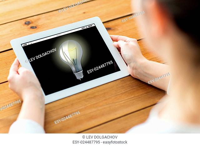 technology, people, business, idea and startup concept - close up of woman with light bulb on tablet pc computer screen on wooden table