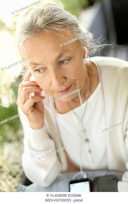 Portrait of senior woman with cell phone and earphones