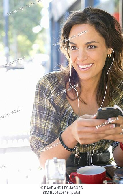 Mixed race woman listening to headphones in cafe