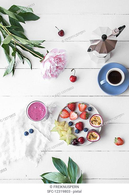 Fresh fruits served on a plate with coffee and a smoothie