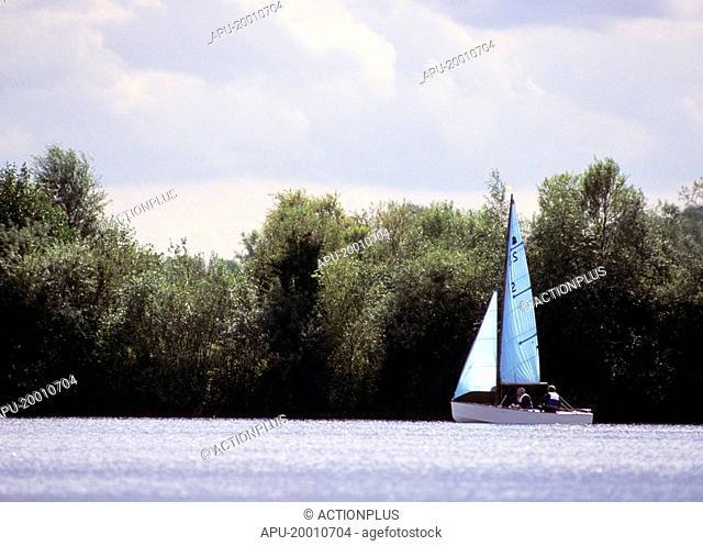 Saling boat sails across a calm lake