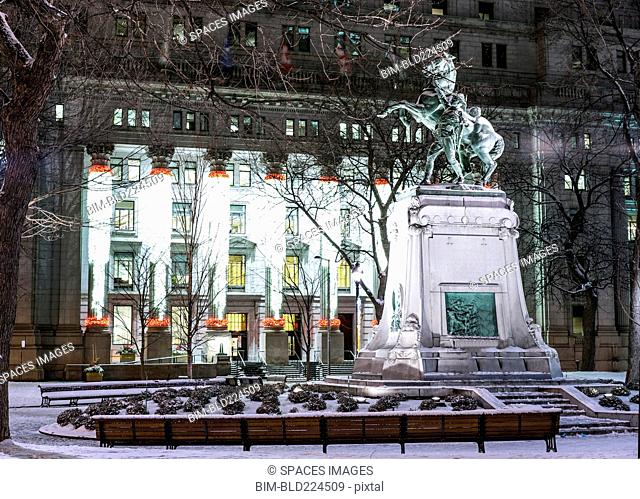 Snow on statue in city at night