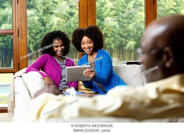 Black father watching mother and daughter using digital tablet on sofa