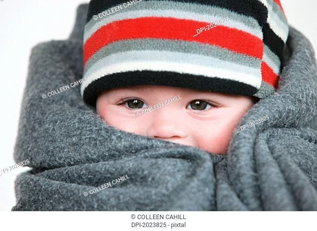 baby wrapped in a grey blanket with a striped hat, troutdale oregon united states of america