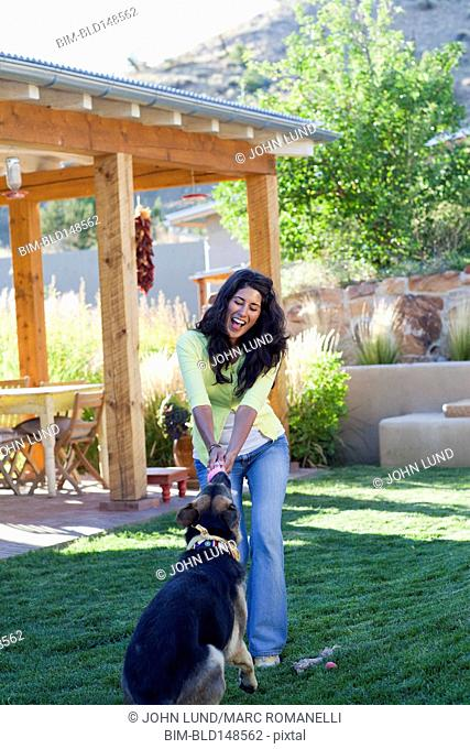 Hispanic woman playing with dog in backyard
