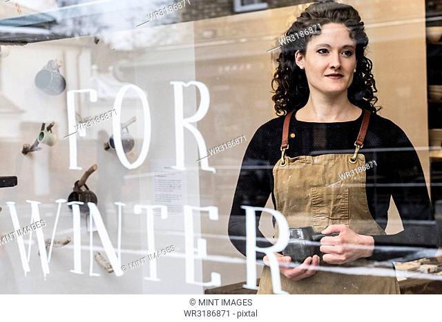 Woman with brown curly hair wearing apron standing behind window of pottery shop, holding mug