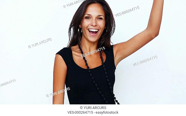 Beautiful young woman dancing happily while isolated on a white background