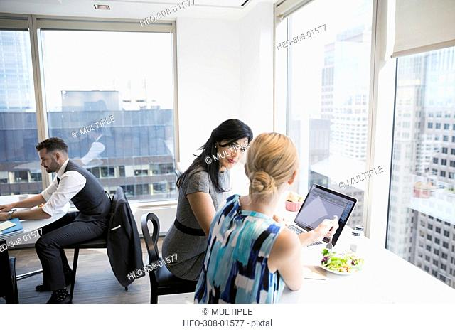 Businesswomen using laptop eating lunch at urban office cafeteria