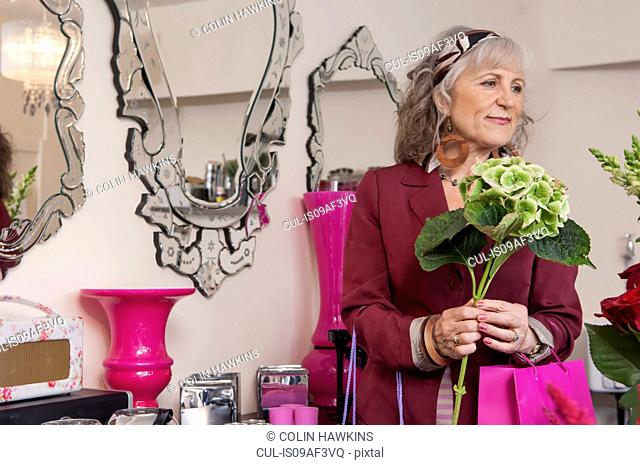 Senior woman with flowers in florist shop