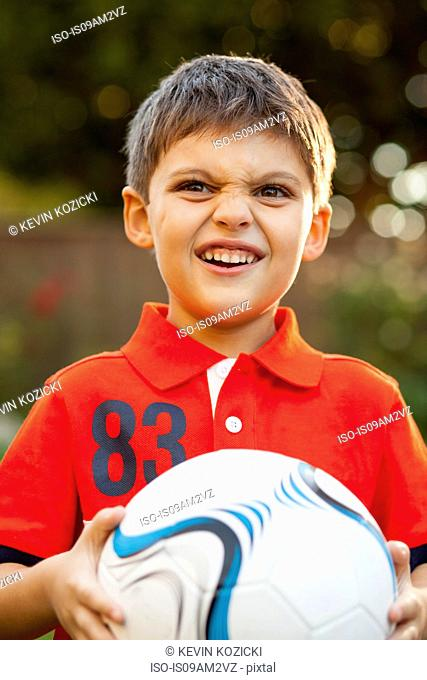 Boy with football, making faces