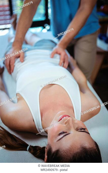 Male physiotherapist giving waist massage to female patient