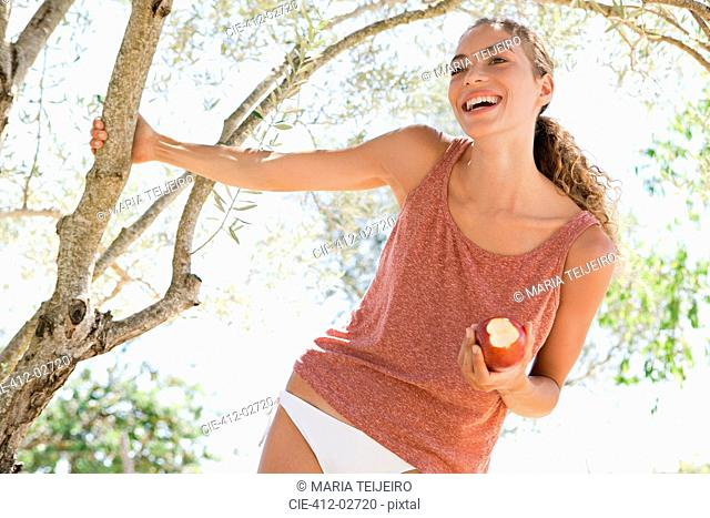 Smiling woman eating apple outdoors