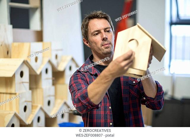 Man holding unfinished birdhouse in workshop
