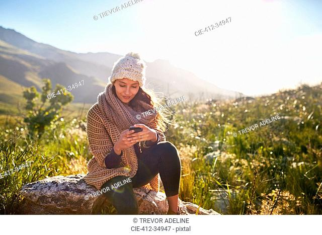 Young woman texting with cell phone on rock in sunny, remote field