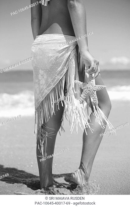 Girl holding starfish on beach, Midriff and legs Black and white photograph