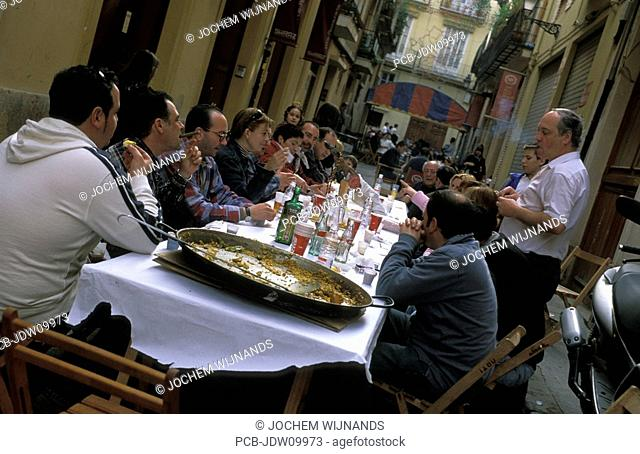Valencia, a group eating paella outside at a long table in a small street