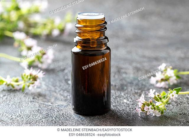 A bottle of essential oil with fresh blooming thyme