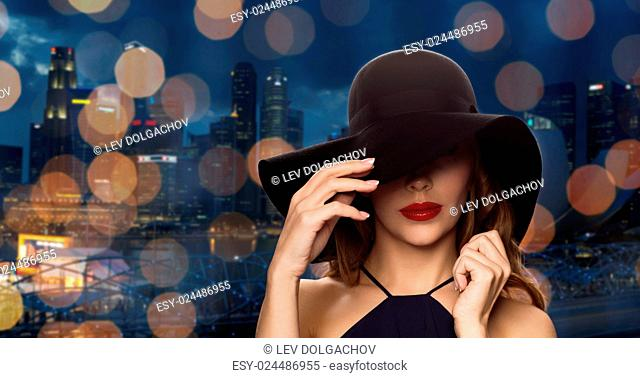 people, luxury and fashion concept - beautiful woman in black hat over night singapore city and lights background