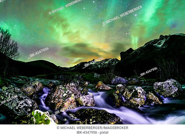 Aurora borealis over landscape with small river near the Sethaugelva lake in Tromvik, Norway