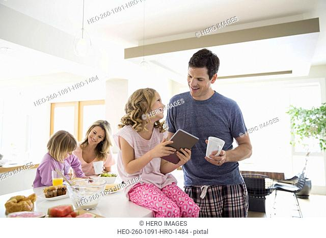 Family with digital tablet eating breakfast in kitchen