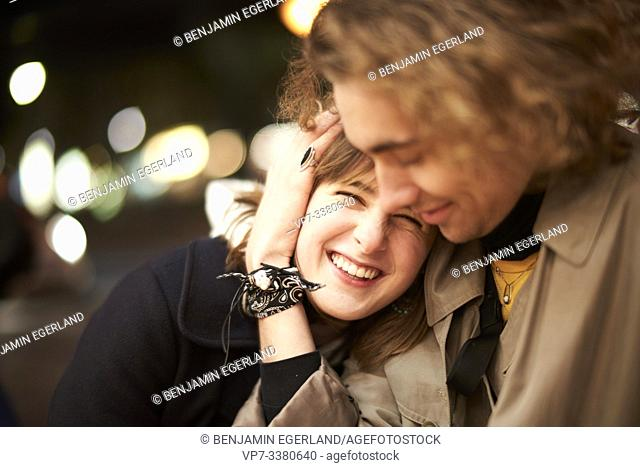 woman laughing in arms of man at night, in Berlin, Germany