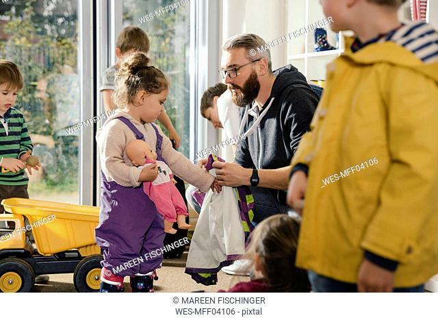 Pre-school teacher helping girl putting on rainwear in kindergarten