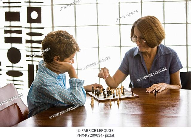 Woman playing chess with her grandson