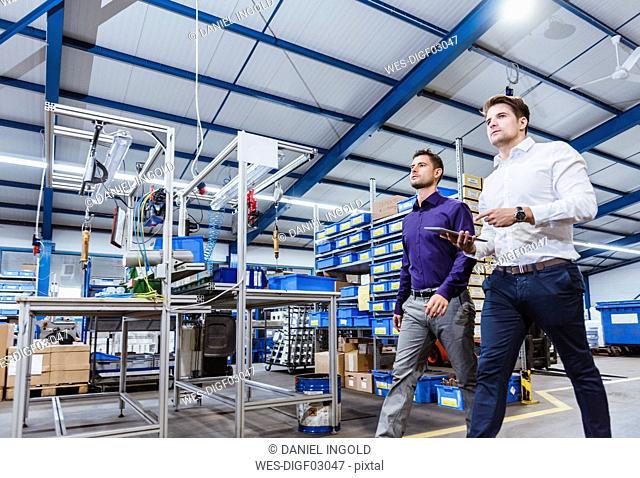 Two business people walking through shop floor. holding digital tablet