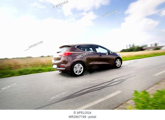 Car moving on country road against cloudy sky