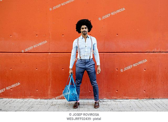 Portrait of fashionable man with bag standing in front of a red wall