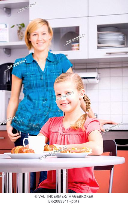 Mother and daughter having breakfast in the kitchen