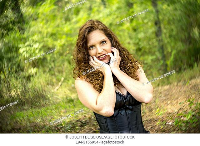 A pretty 39 year old redheaded woman smiling at the camera