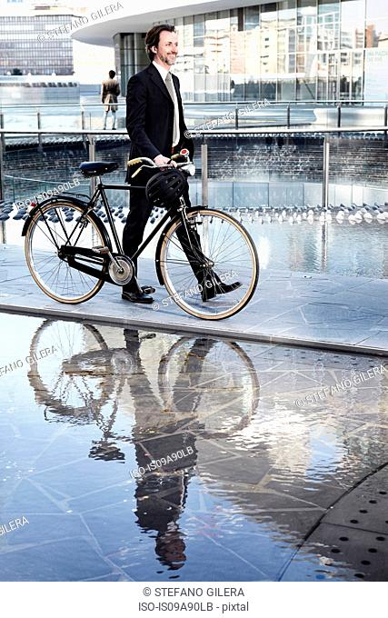 Mid adult businessman walking with bicycle by water feature in city