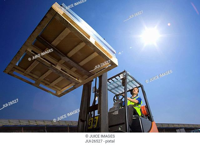 Worker moving merchandise on forklift