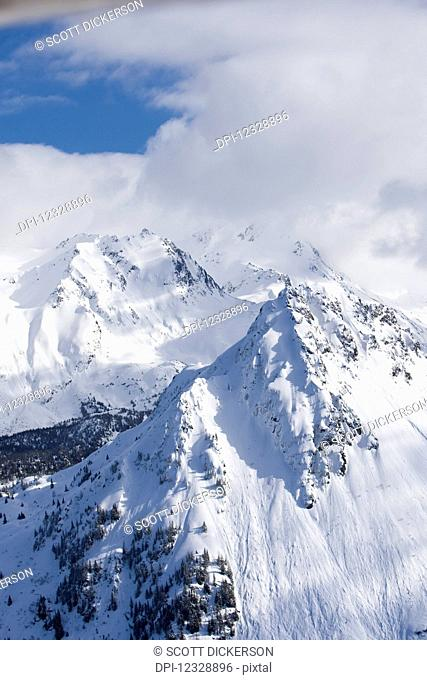 Snow Covered Kenai Mountains With Blue Sky Peaking Out From The Clouds, Kachemak Bay State Park; Alaska, United States Of America
