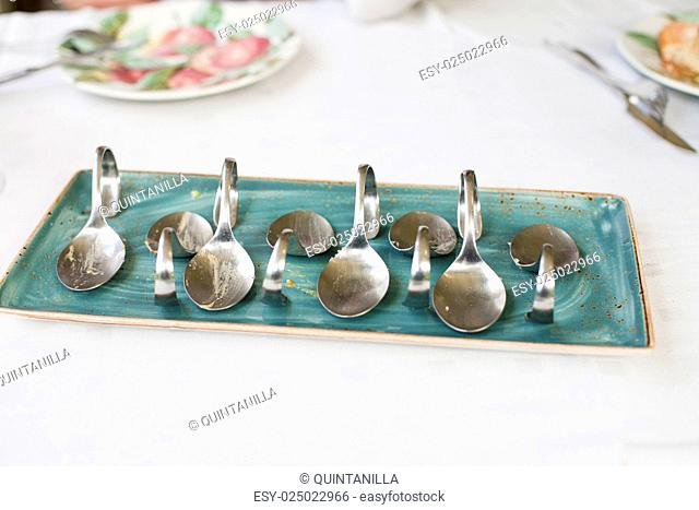 still life of ceramic green dish tray with eight metal curved spoons empty just eaten on restaurant white table