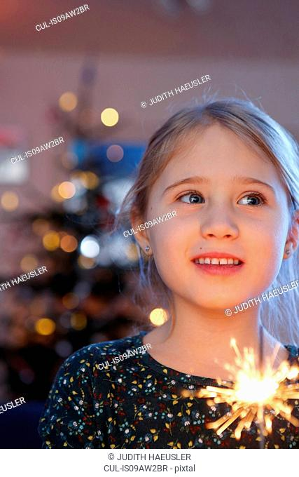 Girls in front of christmas tree holding sparkler looking away smiling