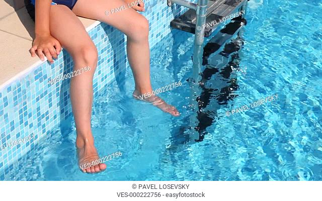 Close-up boys feet in water of pool, stair is near