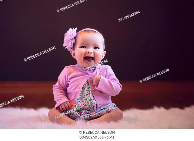 Baby girl sitting on rug wearing flower head band looking at camera mouth open smiling