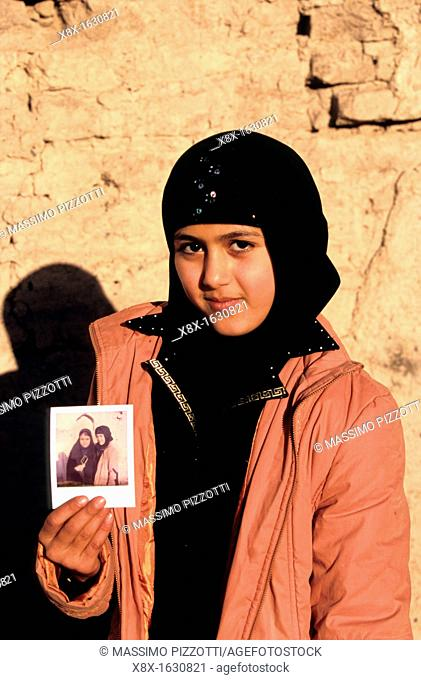 Portrait of young iranian girl showing a polaroid, Iran