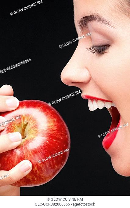 Woman eating a red apple and smiling
