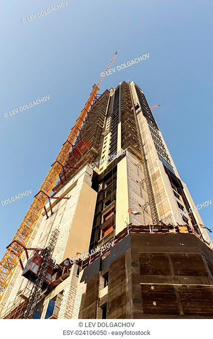 construction, development, architecture, industry and engineering concept - building of skyscraper in Dubai city