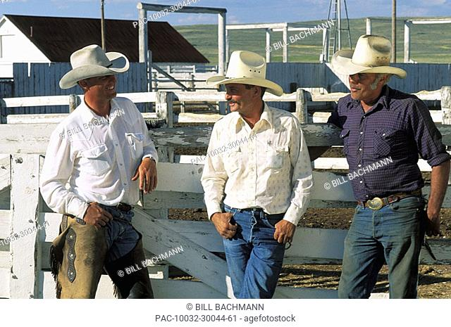 Three cowboys leaning against /nwhite fence near stables, Wearing long sleeve shirts, jeans and cowboy hats